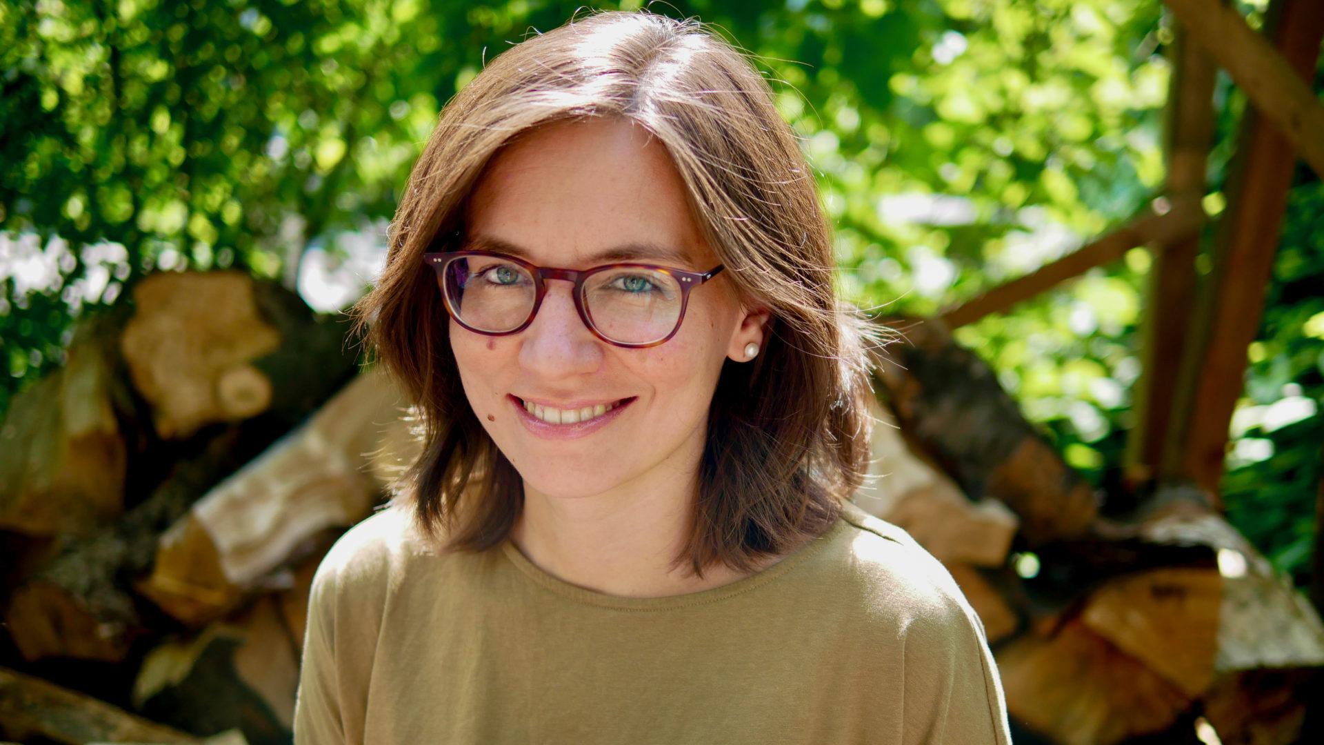 Frau mit braunen Haaren und Brille lächelt in die Kamera